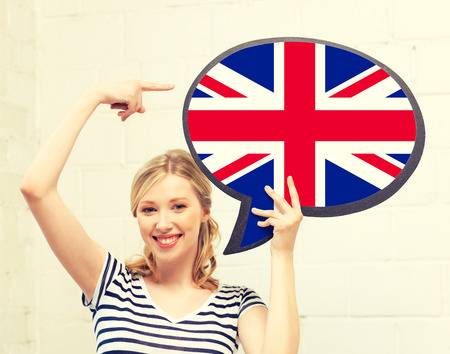 Photo for education, foreign language, english, people and communication concept - smiling woman holding text bubble of british flag and pointing finger - Royalty Free Image