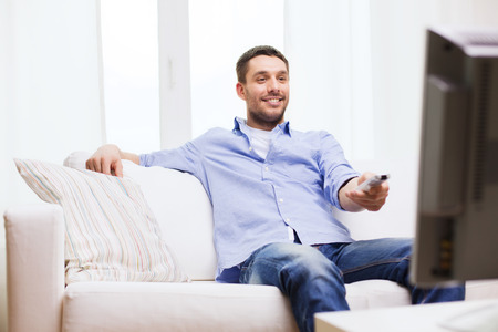 Foto de home, technology, people and entertainment concept - smiling man with tv remote control at home - Imagen libre de derechos