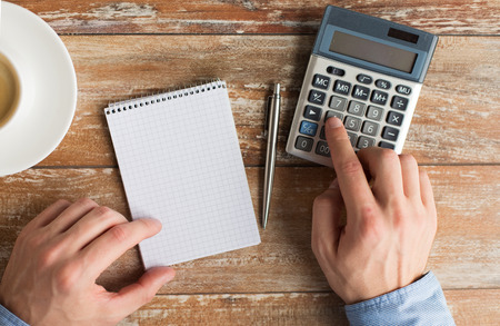 Photo pour business, education, people and technology concept - close up of male hands with calculator, pen and notebook on table - image libre de droit