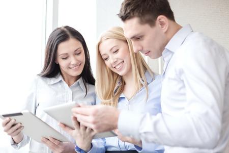 Foto de business and office concept - smiling business team working with tablet pcs in office - Imagen libre de derechos