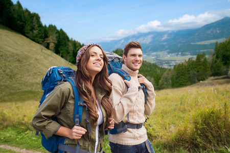 Foto per adventure, travel, tourism, hike and people concept - smiling couple walking with backpacks over alpine hills background - Immagine Royalty Free