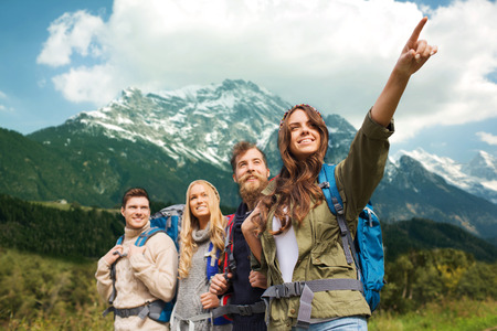 Foto de adventure, travel, tourism, hike and people concept - group of smiling friends with backpacks pointing finger over alpine mountains background - Imagen libre de derechos