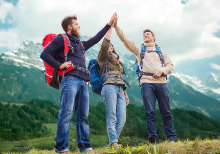 Photo for travel, tourism, hike, gesture and people concept - group of smiling friends with backpacks making high five over alpine mountains background - Royalty Free Image