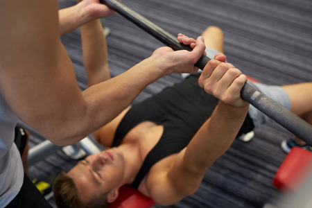 Foto de sport, fitness, teamwork, weightlifting and people concept - young man and personal trainer with barbell flexing muscles in gym - Imagen libre de derechos