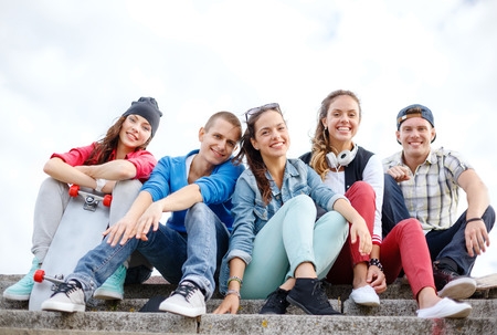 Photo pour summer holidays and teenage concept - group of smiling teenagers hanging outside - image libre de droit