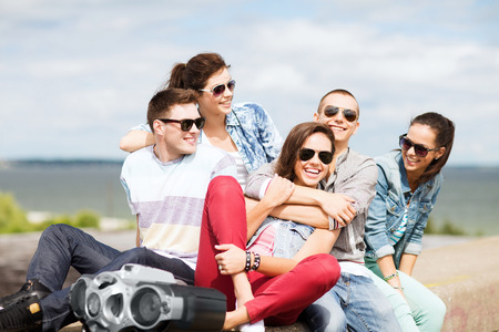 Photo for summer holidays and teenage concept - group of teenagers hanging out - Royalty Free Image