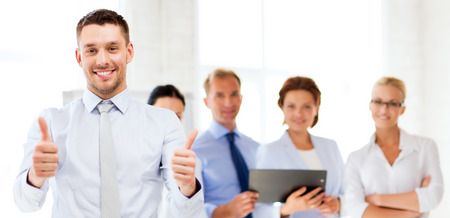 Foto de attractive businessman in office showign thumbs up - Imagen libre de derechos