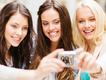 Foto de holidays and tourism concept - beautiful girls taking picture in cafe in city - Imagen libre de derechos