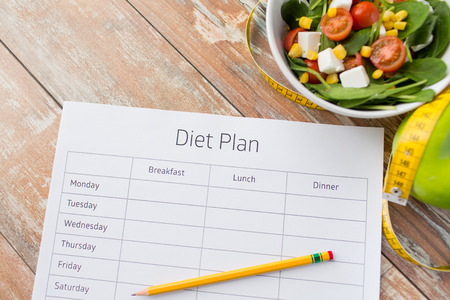 Foto de healthy eating dieting slimming and weigh loss concept  close up of diet plan paper green apple measuring tape and salad - Imagen libre de derechos