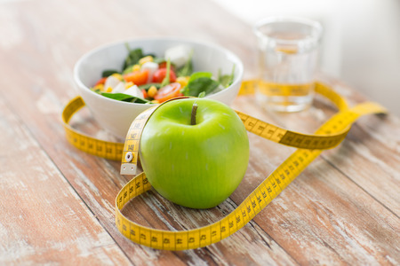healthy eating dieting slimming and weigh loss concept  close up of green apple measuring tape and salad