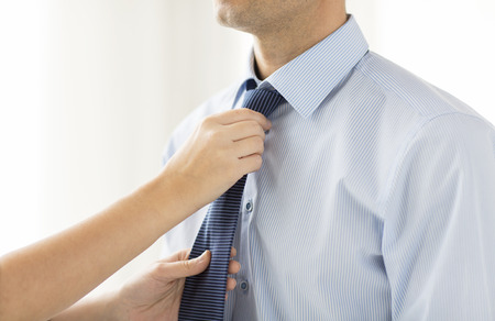 Foto de people, business, care and clothing concept - close up of woman helping man and adjusting tie on his neck at home - Imagen libre de derechos