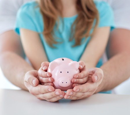 Foto de family, children, money, investments and people concept - close up of father and daughter hands holding pink piggy bank - Imagen libre de derechos