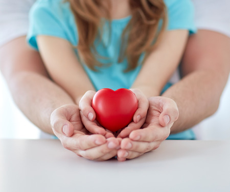 Foto de people, charity, family and advertisement concept - close up of father and girl holding red heart shape in cupped hands at home - Imagen libre de derechos