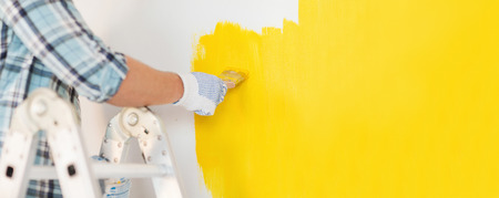 Photo for repair and home renovation concept - close up of male hand in gloves painting a wall with yellow paint - Royalty Free Image
