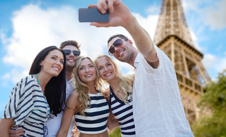 Photo pour summer, france, tourism, technology and people concept - group of smiling friends taking selfie with smartphone over eiffel tower in paris background - image libre de droit