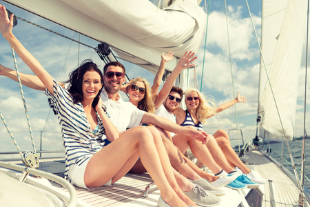 Foto de vacation, travel, sea, friendship and people concept - smiling friends sitting on yacht deck and greeting - Imagen libre de derechos