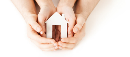 Foto de real estate and family home concept - closeup picture of male and female hands holding white blank paper house - Imagen libre de derechos