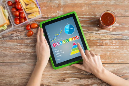 Foto de healthy eating, vitamins, dieting, technology and people concept - close up of woman hands with tablet pc computer and food in plastic container on table counting calories at home - Imagen libre de derechos