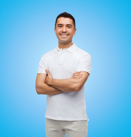 Photo for happiness and people concept - smiling man in white t-shirt with crossed arms over blue background - Royalty Free Image