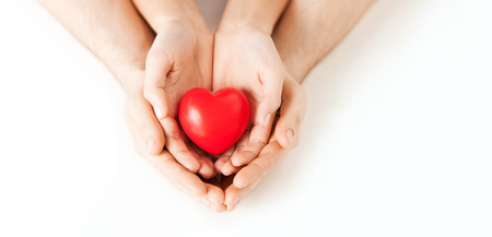 Foto de health, love and relationships concept - closeup of couple hands with big red heart - Imagen libre de derechos