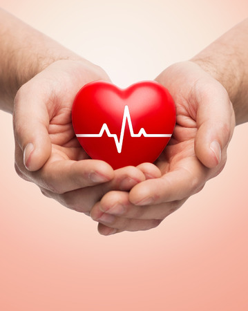 Foto de family health, charity and medicine concept - close up of hands holding red heart with cardiogram over beige background - Imagen libre de derechos