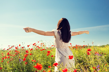 Foto de happiness, nature, summer, vacation and people concept - young woman dancing on poppy field from back - Imagen libre de derechos