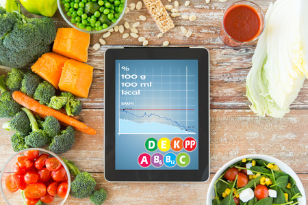 Foto de healthy eating, dieting, calories counting and weigh loss concept - close up of tablet pc screen with chart and vegetables on table - Imagen libre de derechos