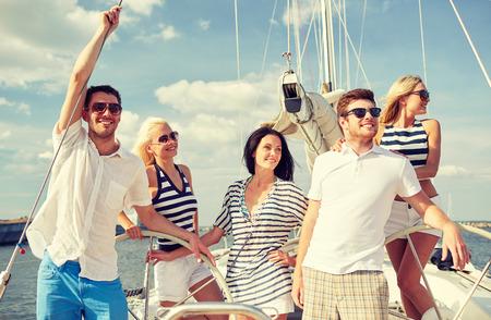Photo pour vacation, travel, sea, friendship and people concept - smiling friends sailing on yacht - image libre de droit