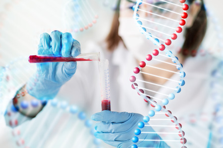 Foto de science, chemistry, biology, medicine and people concept - close up of female scientist holding tube with blood sample making and test or research in clinical laboratory over dna molecule structure - Imagen libre de derechos