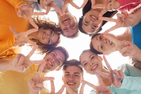 Photo pour friendship, youth, gesture and people - group of smiling teenagers in circle showing victory sign - image libre de droit