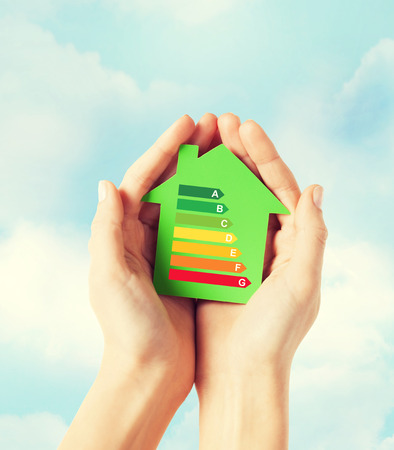 Foto de energy saving, real estate and family home concept - closeup of female hands holding green paper house with energy efficiency rating - Imagen libre de derechos