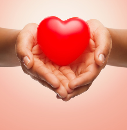 Foto de health, medicine, love, valentines day and charity concept - close up of african american female hands holding small red heart over beige background - Imagen libre de derechos