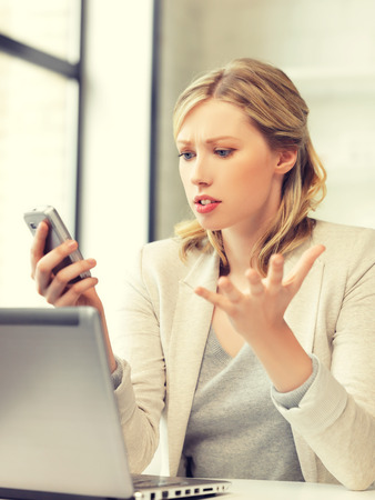 Photo for picture of confused woman with cell phone - Royalty Free Image
