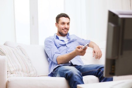 Photo pour home, technology, people and entertainment concept - smiling man with tv remote control at home - image libre de droit