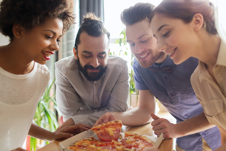 Foto per business, food, lunch and people concept - happy business team eating pizza in office - Immagine Royalty Free