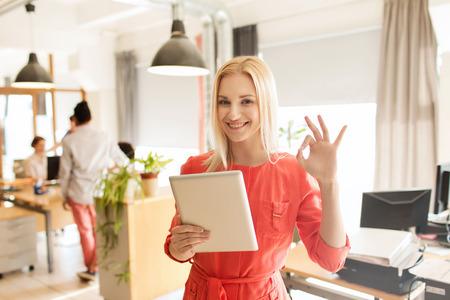 Foto de business, startup and people concept - happy businesswoman or creative female office worker with tablet pc computer showing ok hand sign - Imagen libre de derechos