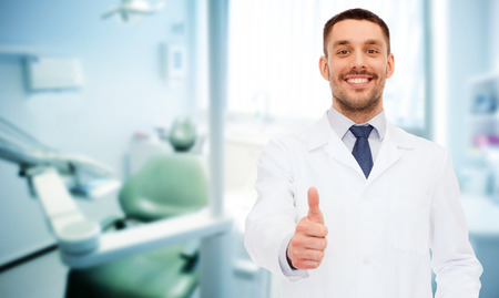 Foto de healthcare, profession, stomatology and medicine concept - smiling male dentist showing thumbs up over medical office background - Imagen libre de derechos