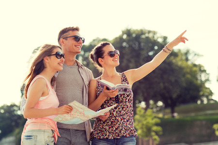 Photo for friendship, travel, tourism, vacation and people concept - smiling friends with map and city guide pointing finger outdoors - Royalty Free Image