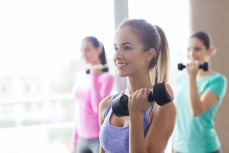 Foto für fitness, sport, training and lifestyle concept - group of happy women with dumbbells flexing muscles in gym - Lizenzfreies Bild
