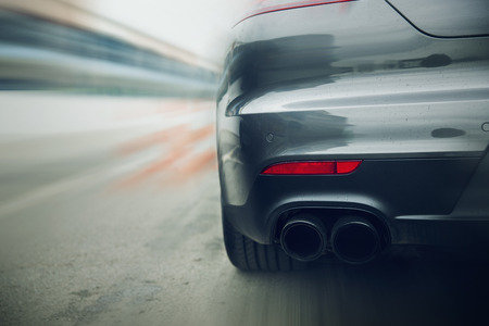 Photo pour transportation, speed, racing and road concept - close up of car riding on highway from back - image libre de droit