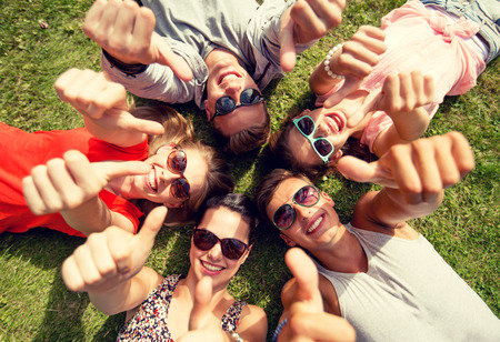 Foto de friendship, leisure, summer, gesture and people concept - group of smiling friends lying on grass in circle and showing thumbs up outdoors - Imagen libre de derechos