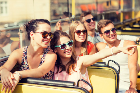 Foto de friendship, travel, vacation, summer and people concept - group of smiling friends traveling by tour bus - Imagen libre de derechos