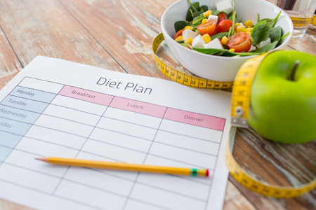 Foto de healthy eating, dieting, slimming and weigh loss concept - close up of diet plan paper green apple, measuring tape and salad - Imagen libre de derechos