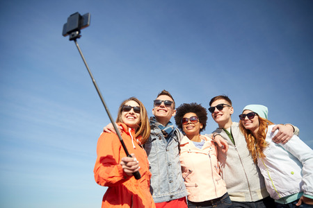 Photo pour tourism, travel, people, leisure and technology concept - group of smiling teenage friends taking selfie with smartphone and monopod outdoors - image libre de droit