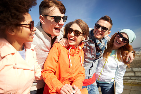Foto de tourism, travel, people, leisure and teenage concept - group of happy friends in sunglasses hugging and laughing on city street - Imagen libre de derechos