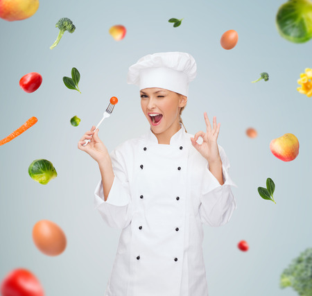 Foto per cooking and food concept - smiling female chef, cook or baker with fork and tomato showing ok sign over falling vegetables on gray background - Immagine Royalty Free