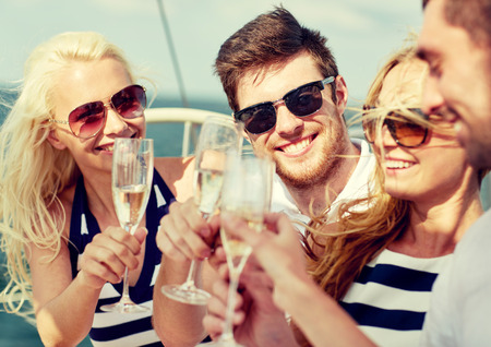 Foto de vacation, travel, sea, friendship and people concept - smiling friends with glasses of champagne on yacht - Imagen libre de derechos