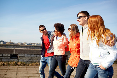 Photo for tourism, travel, people and leisure concept - group of happy teenage friends walking along city street and talking - Royalty Free Image