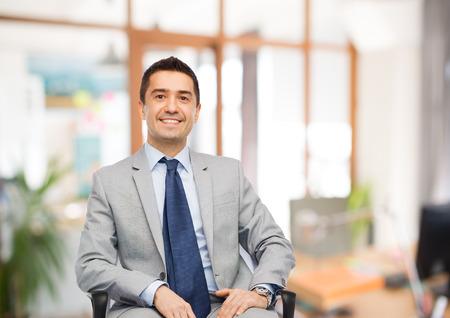 Foto de business, people and office concept - happy businessman in suit sitting in chair over office room background - Imagen libre de derechos