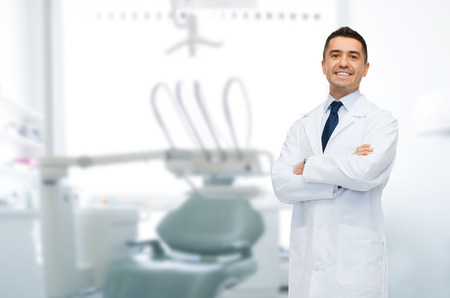 Foto de healthcare, profession, stomatology and medicine concept - smiling male middle aged dentist over medical office background - Imagen libre de derechos